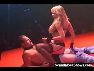 Naughty big breasted blonde gives her victim a live lap dance on stage while the public watches