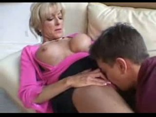 This mature women fucks a younger man on a couch