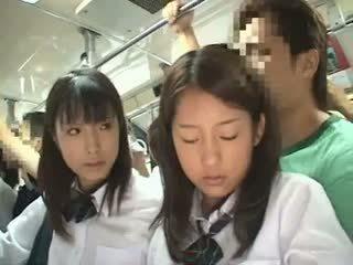 Two schoolgirls apgraibytas į a autobusas